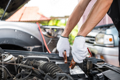 Close up of man hand charging a car battery using electricity trough jumper cables Fototapet