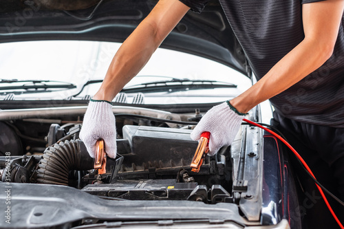 Close up of man hand charging a car battery using electricity trough jumper cables фототапет