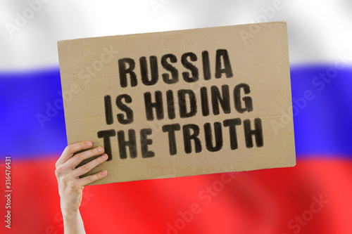 The phrase  Russia is hiding the truth  on a banner in men's hand with blurred Russian flag on the background Canvas Print