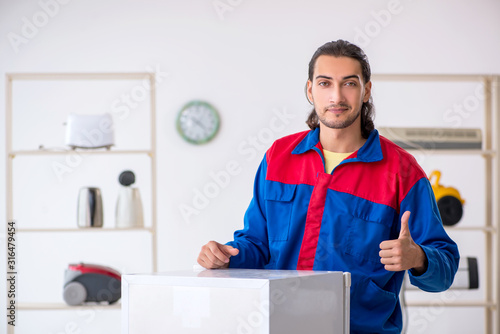 Fototapety, obrazy: Young male contractor repairing refrigerator at workshop
