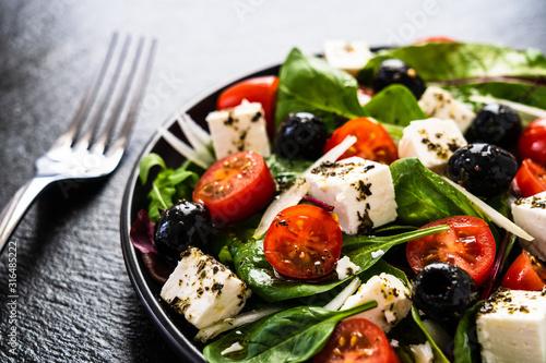 Photo Fresh greek salad - feta cheese, tomato, lettuce, black olives and onion