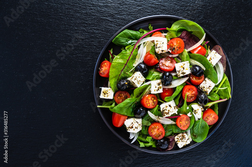 Cuadros en Lienzo Fresh greek salad - feta cheese, tomato, lettuce, black olives and onion