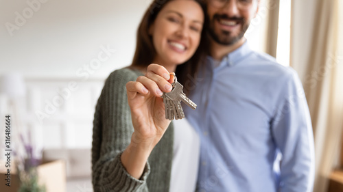 Smiling young couple show house keys moving in together