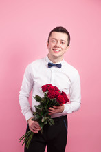 Handsome Man Holding Red Flowers Over Pink Background And Looking At Camera