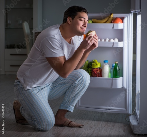 Photo Man at the fridge eating at night