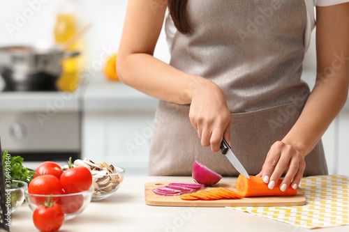 Fotografía Young woman cutting vegetables for soup at table in kitchen, closeup