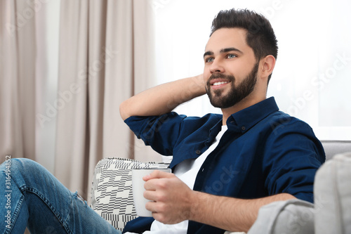 Fotografie, Obraz Young man with cup of drink relaxing on couch at home