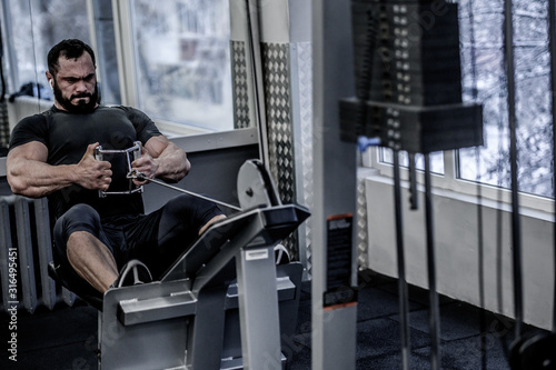 powerful young athlete man with beard pulling heavy weight sitting in sport fitn Fototapeta