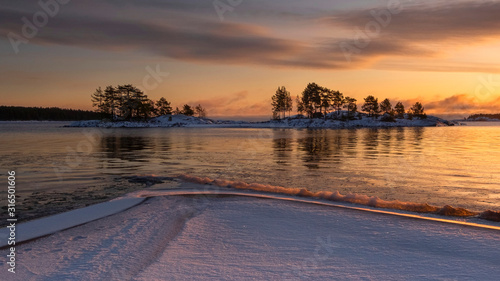 silhouettes of islands and trees on the winter Lake Ladoga in Karelia Russia at Fototapeta