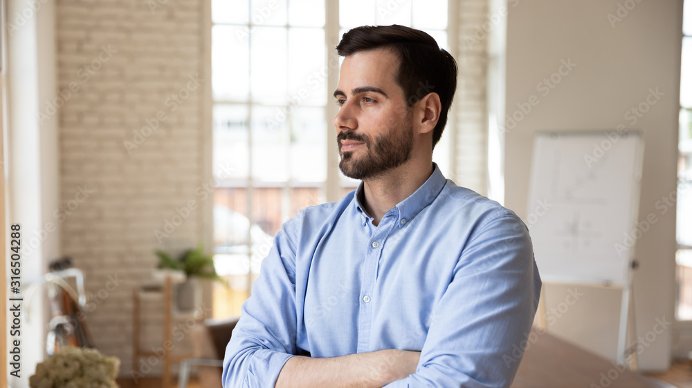 Fototapeta Thoughtful confident businessman looking in distance, pondering strategy