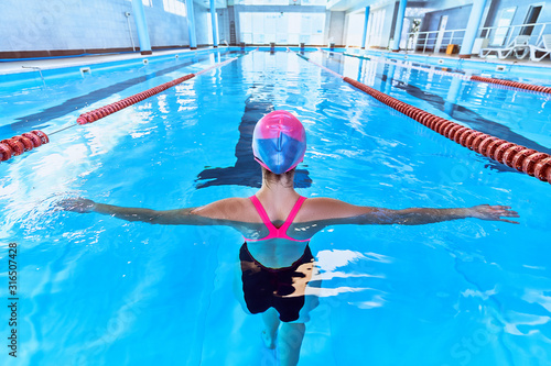Fototapeta Sporty athletic fitness swimmer woman in swimsuit and swimming hat during swimmi