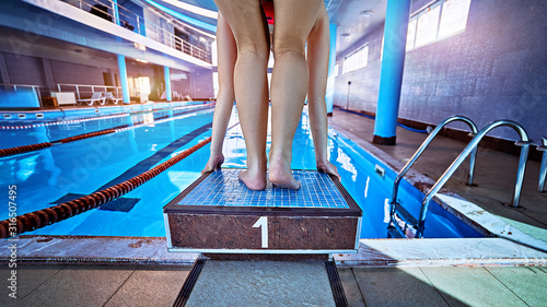 Cuadros en Lienzo  Sporty athletic female champion swimmer in low position on starting block in a s