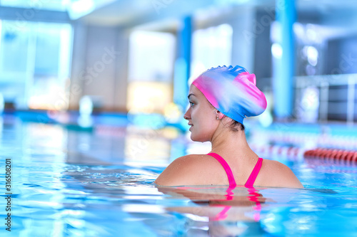 Fototapety, obrazy: Sporty fit woman in swimming hat and swimsuit learns to swim in sports pool in leisure center
