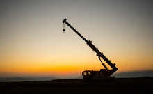 Abstract Industrial Background With Construction Crane Silhouette Over Amazing Sunset Sky. Tower Crane Against The Evening Sky. Industrial Skyline. Selective Focus