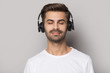 Handsome guy wearing modern wireless headphones, enjoying favorite slow music.