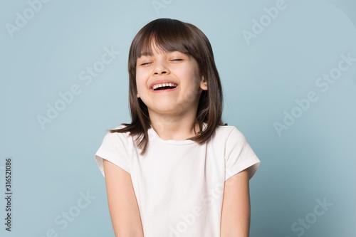 Obraz Happy preschool cutie laughing, joking, posing on blue background. - fototapety do salonu
