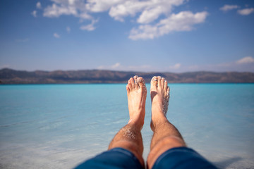 Man foot at summer blue beach
