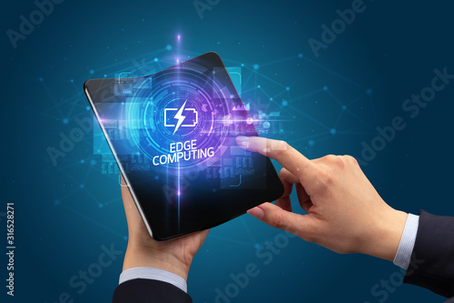 Fototapeta Businessman holding a foldable smartphone with INNOVATIONS inscription, new technology concept EDGE COMPUTING obraz