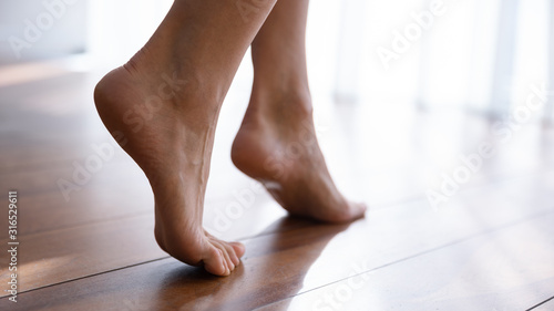 Close up side view beautiful female feet on wooden floor Canvas Print
