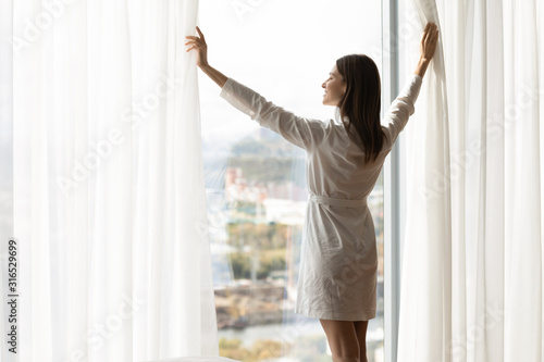 Smiling beautiful woman starting new day, opening curtains