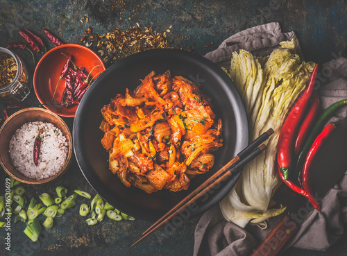 Fotografia Homemade kimchi in black bowl on rustic background with ingredients: chinese cabbage , chili, spices and salt