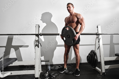 Portrait of muscular strong athletic man with naked torso pumping up muscles in Fototapeta