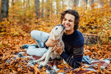 Photo Of Handsome Man And His  Labrador Playing Together In The Autumn Forest.