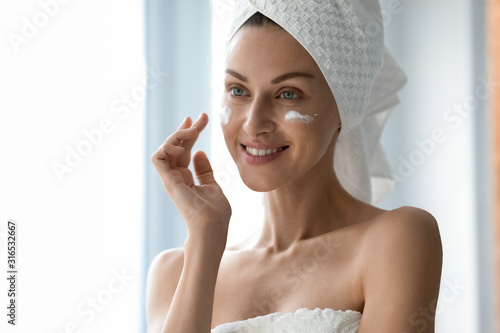 Fotografie, Obraz Beautiful woman with healthy smile applying cream on cheeks