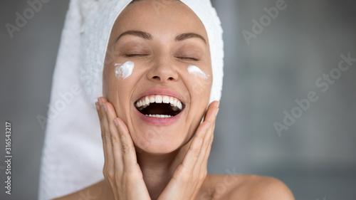 Fototapeta Close up excited beautiful woman laughing, applying moisturizing cream