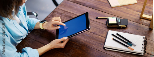 Obraz Mockup image of a woman using digital tablet with blank screen on wooden table. Close up photo of female hands holding device vertically - fototapety do salonu