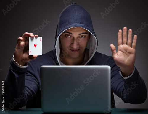 Papel de parede Young man wearing a hoodie sitting in front of a laptop computer