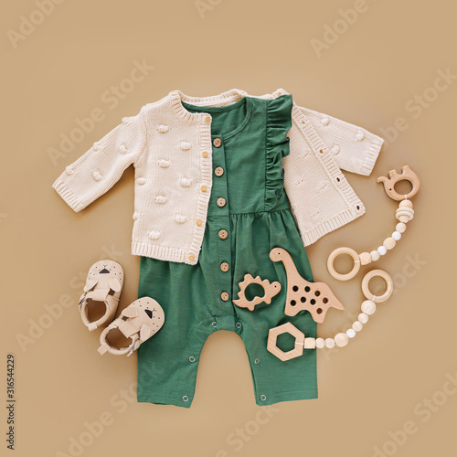 Green romper  with knitted  jumper, wooden toys and baby shoes. Set of baby clothes and accessories on beige background.  Fashion newborn. Flat lay, top view Wall mural