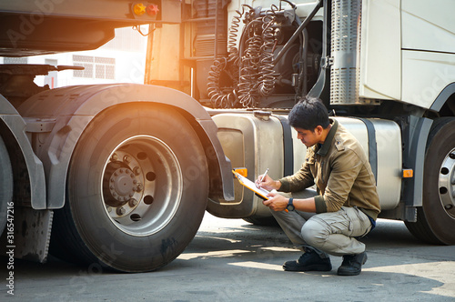 Cuadros en Lienzo Truck driver asian holding clipboard inspecting safety vehicle maintenance check