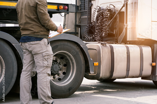 Truck driver holding clipboard inspecting vehicle maintenance checklist of semi truck Canvas Print