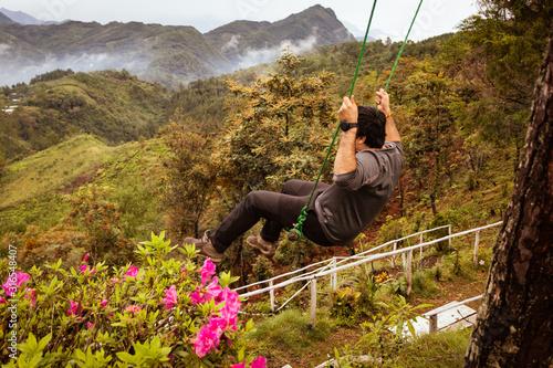 Photo Joven en un columpio con flores al rededor en la montaña