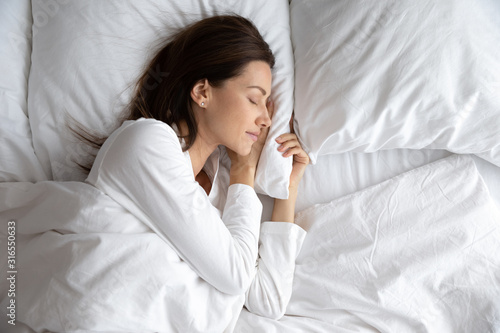 Photo Serene beautiful woman sleeping with hand under cheek on pillow