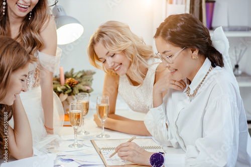 group caucasian models have conversation with designer and tailor of wedding dre Canvas Print