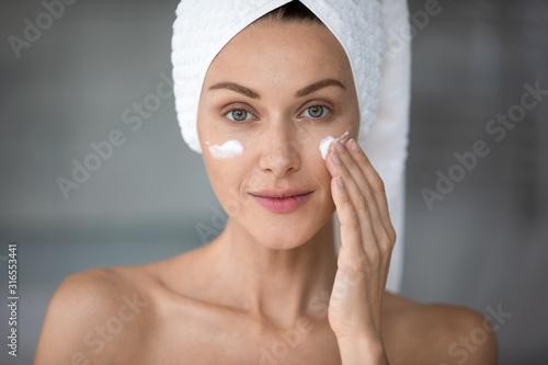 Carta da parati Head shot portrait beautiful woman applying cream on cheekbones
