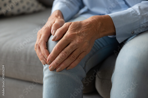 Close up older woman touching knee with hands, feeling pain Canvas Print