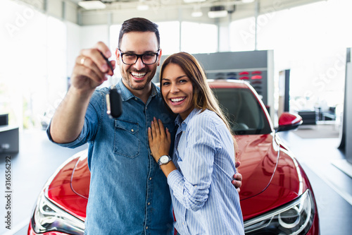 mata magnetyczna Beautiful young smiling couple holding a key of their new car.