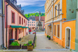 Fototapeta Uliczki - Narrow street of Loket town with colorful traditional typical buildings, street flowers and Column of the Holy Trinity at Marketplace square, Karlovy Vary Region, West Bohemia, Czech Republic
