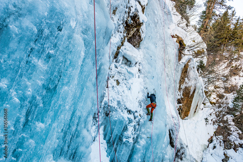 Ice Climbing Woman with an Ice Axe and Crampons on a Frozen Waterfall in the Tas Canvas Print