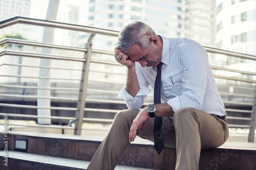 Photo Depressed senior businessman in city