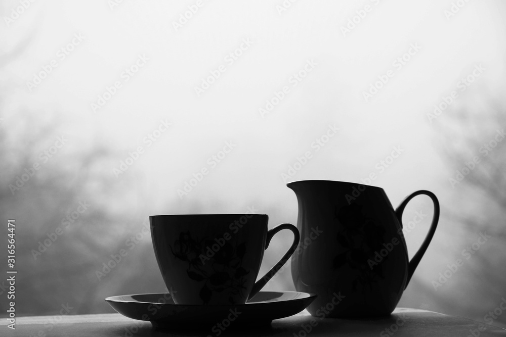 Fototapeta Black and white still life with cup, saucer and jug for milk on blurred background. Misty day in Ukraine. Loneliness concept. Copy space.