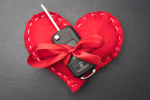 Car Key With Red Bow And A Heart On Dark Black Slate Plate Background. Christmas Or Valentine's Day Gift Or Present Abstract Concept. Flat Lay Top View.