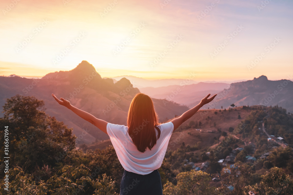 Fototapeta Young woman traveler looking at sunset over the mountain