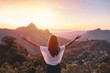 canvas print picture - Young woman traveler looking at sunset over the mountain