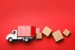 canvas print picture - Top view of toy truck with boxes on red background. Logistics and wholesale concept