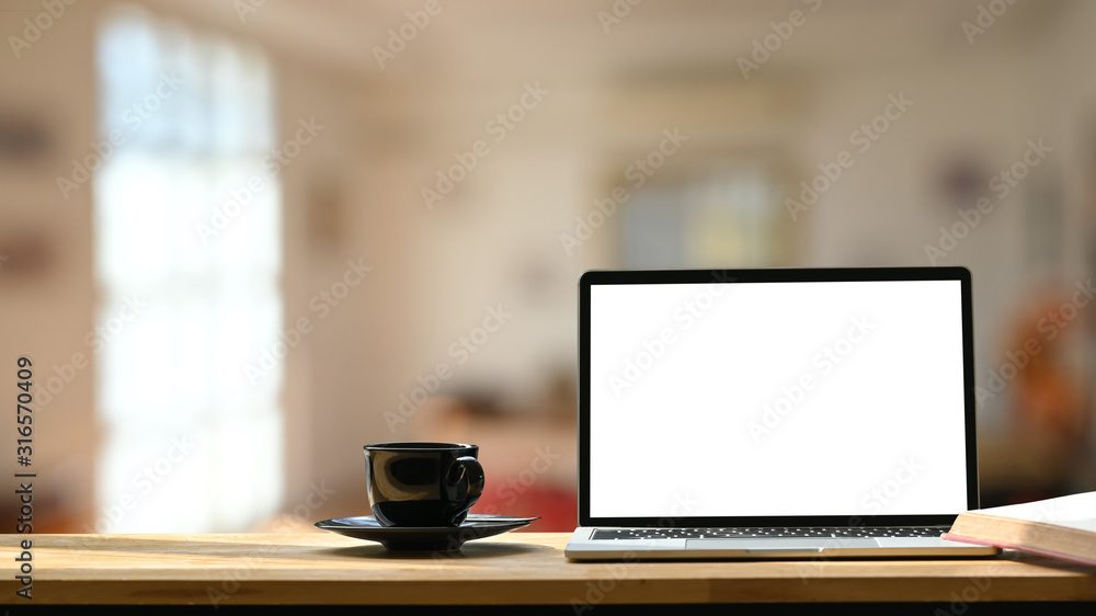 Fototapeta Photo of white blank screen laptop, black coffee cup and coasters on the wooden working desk over blurred modern cafe background.