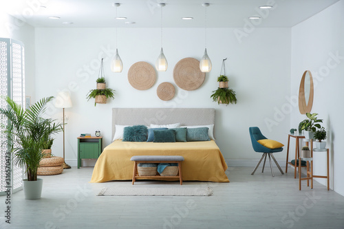 Fototapeta Stylish room interior with large comfortable bed obraz
